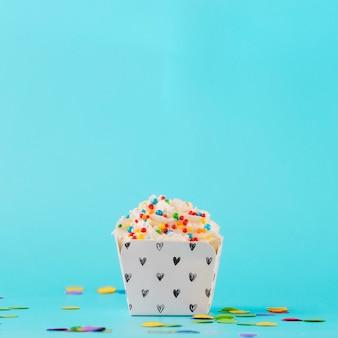Panna montata bianca con confettini colorati e coriandoli su sfondo blu