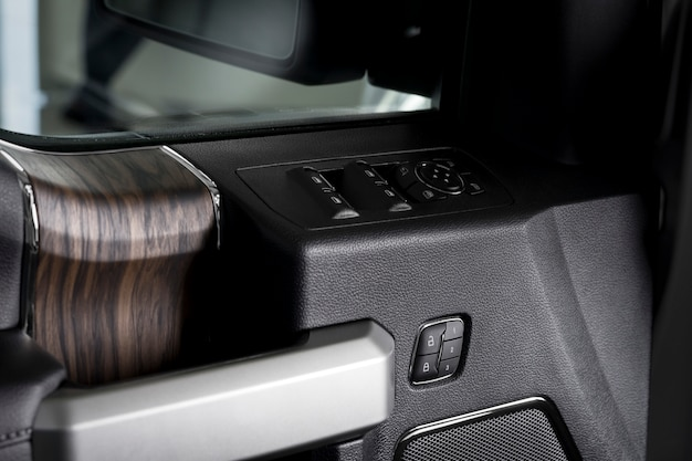 Pannello porta elettrica, interno di una nuova auto con dettagli in legno - specchio retrovisore