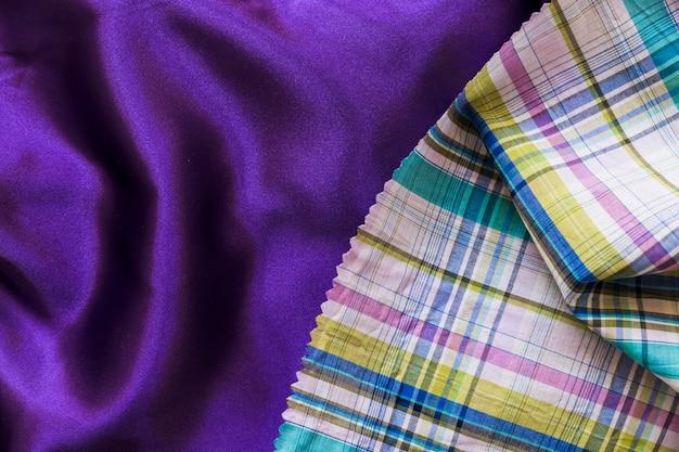 Panno di stoffa a scacchi colorati su un semplice tessuto viola