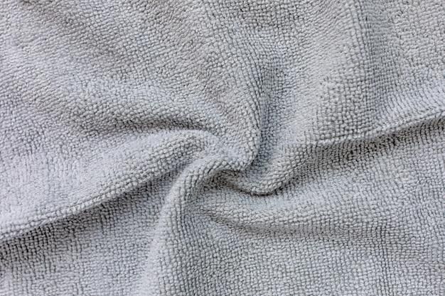 Panno in microfibra grigio per la pulizia. pulizia di asciugamani in micro tessuto per spolvero e lucidatura. concetto di servizio di pulizia domestica. primo piano, copia spazio