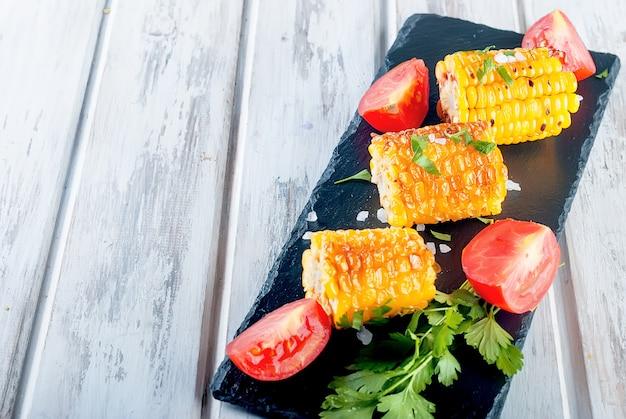 Pannocchie di mais alla griglia con sugo, spezie e pomodori