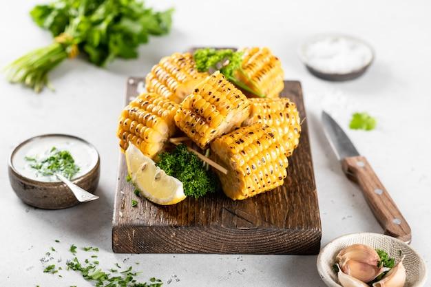 Pannocchie di mais alla griglia su una tavola di cucina su uno sfondo bianco