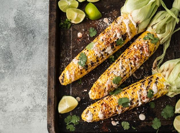 Pannocchie di mais grigliate con salsa, coriandolo, lime, paprika e formaggio. cibo messicano. vista dall'alto. copia spazio
