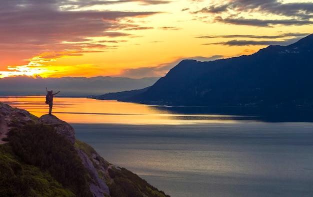 Panorama ampio lago di montagna. piccola siluetta del turista con lo zaino sul pendio di montagna rocciosa con le mani sollevate sull'acqua del lago coperta