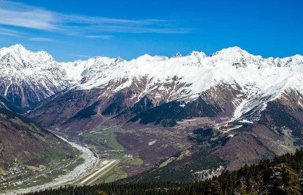 Panorama del villaggio della georgia nel fiume e nella neve delle montagne