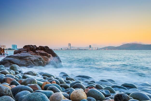 Panorama della città di quy nhon da pebble beach e massi di roccia in primo piano, famosa destinazione turistica in vietnam. baia di quy nhon onde morbide onde lunghe del mare. grattacieli e skyline della città al tramonto
