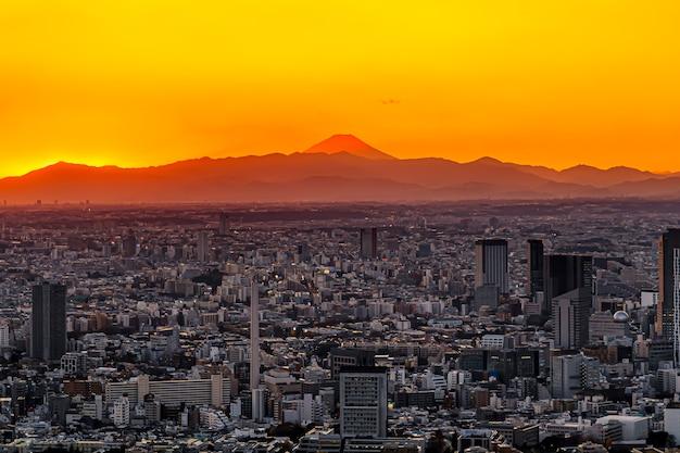 Panorama della città moderna con la costruzione di architettura sotto il cielo crepuscolare della catena montuosa del paesaggio e del picco di montagna di fuji nella città di tokyo, giappone.