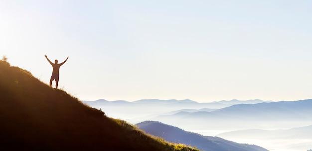 Panorama di giovane riuscito uomo escursionista silhouette a braccia aperte sul picco di montagna.