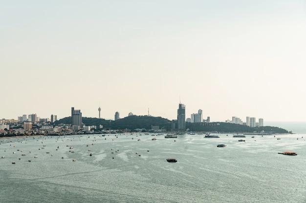 Panorama di paesaggio urbano con edifici di costruzione e vista sul mare con le barche, cielo luminoso della spiaggia di pattaya.