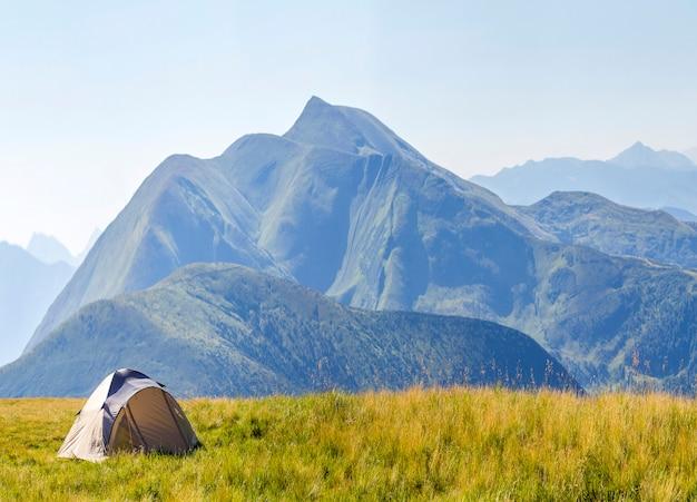 Panorama montano con tenda turistica. alba o tramonto in montagna. concetto di escursionismo.