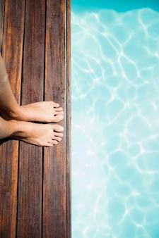 Panoramica dei piedi della donna sul bordo della piscina