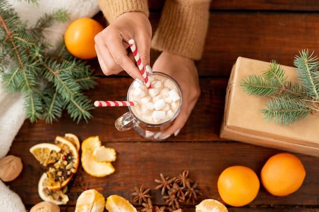 Panoramica delle mani umane che tengono un bicchiere di latte con marshmallow circondato da conifere e arance fresche