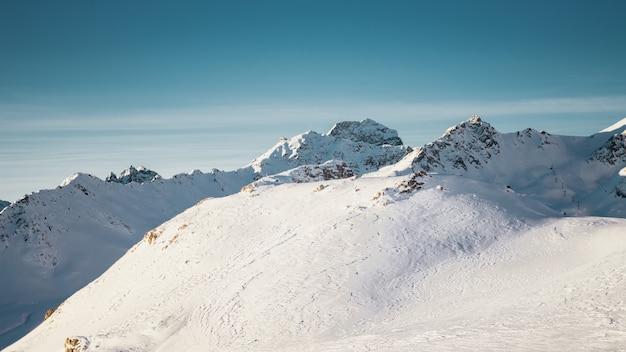 Panoramica delle montagne coperte di neve sotto un cielo blu chiaro con una mezza luna