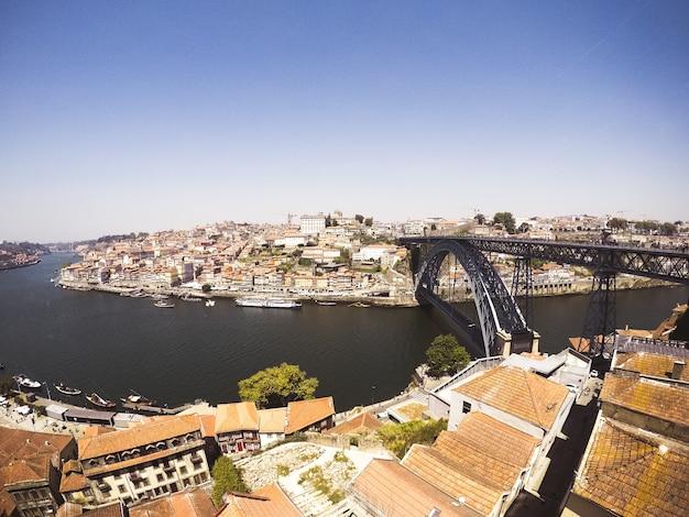 Panoramica di un ponte ad arco nero sul corpo idrico che collega le città sulle rive del lago