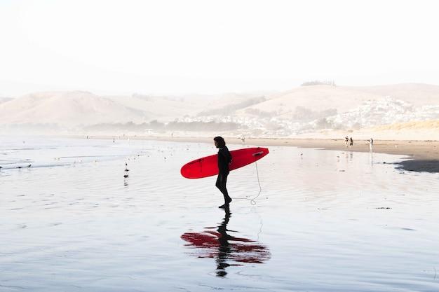 Panoramica di un surfista maschio che indossa tuta da surf tenendo una tavola da surf in riva al mare
