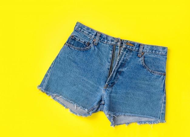 Pantaloncini di jeans classici delle donne alla moda con frange su sfondo giallo brillante.