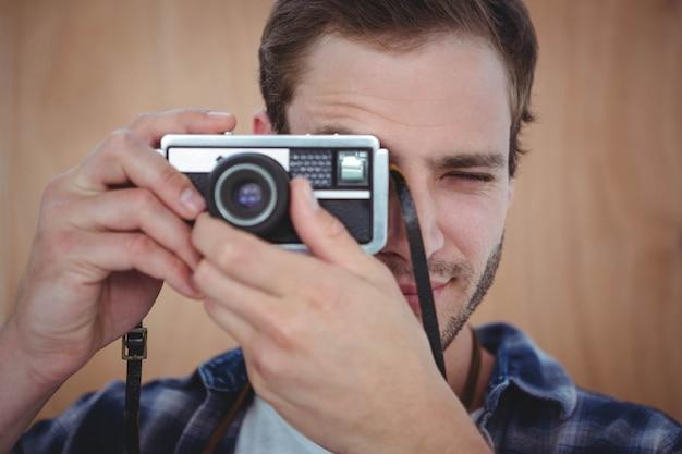 Pantaloni a vita bassa bei che prendono immagine con la retro macchina fotografica