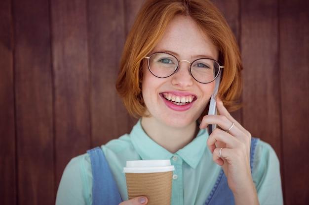 Pantaloni a vita bassa che parlano sul telefono che mangia caffè
