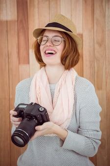 Pantaloni a vita bassa che sorridono e che tengono macchina fotografica
