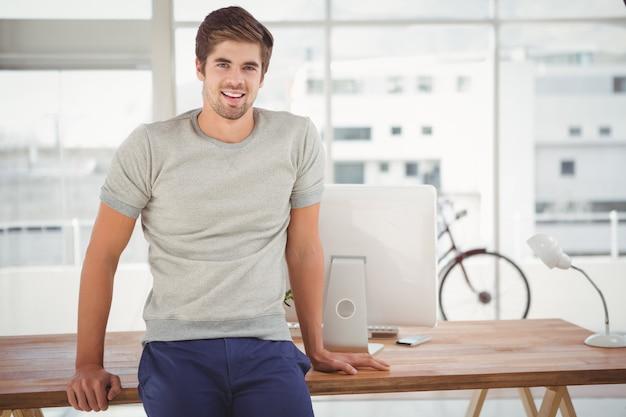 Pantaloni a vita bassa che sorridono mentre appoggiandosi allo scrittorio in ufficio