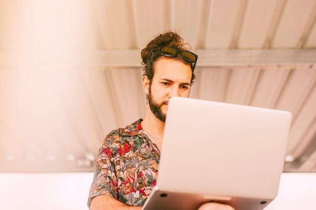 Pantaloni a vita bassa concentrati che lavorano al computer portatile all'aperto