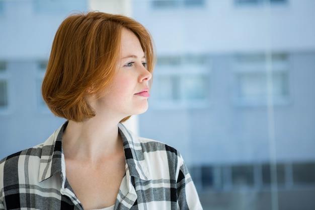 Pantaloni a vita bassa dai capelli rossi che sorridono alla macchina fotografica davanti ad una finestra