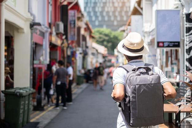 Pantaloni a vita bassa del giovane che viaggiano con lo zaino e il cappello
