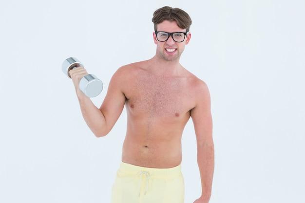 Pantaloni a vita bassa geeky che posa in topless con il dumbbell