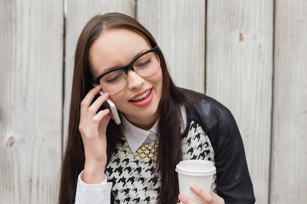Pantaloni a vita bassa graziosi che parlano sul telefono che mangia caffè