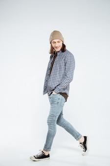 Pantaloni a vita bassa sorridenti che camminano nello studio