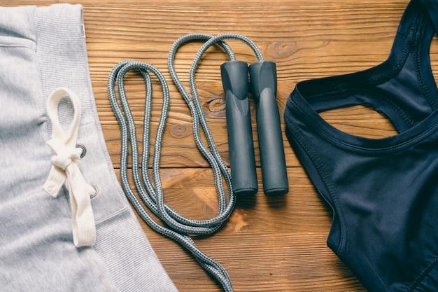 Pantaloni sportivi, un reggiseno sportivo e corda per saltare