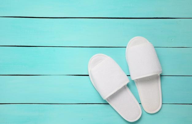 Pantofole bianche dell'hotel su un pavimento di legno blu. vista dall'alto.