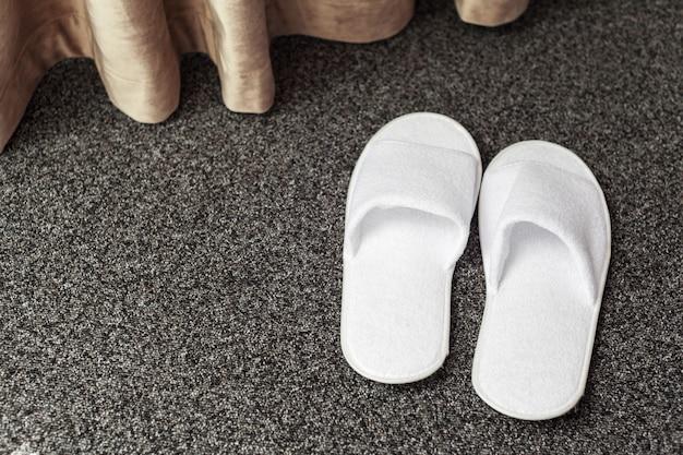 Pantofole sul pavimento della camera d'albergo