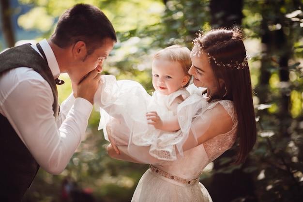 Papà bacia il piede della sua piccola figlia mentre la madre la tiene