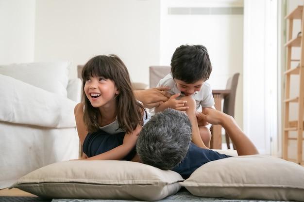 Papà che gioca con i ragazzini attivi eccitati.