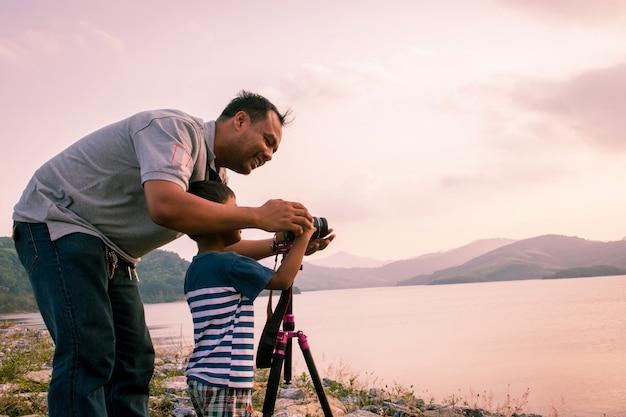 Papà che prepara il ragazzino che cattura la macchina fotografica alla diga