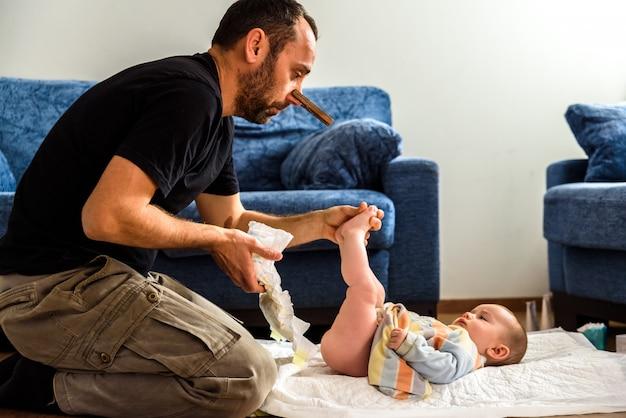 Papà che pulisce il culo sporco del suo bambino, cambiando il pannolino puzzolente con un fermaglio per il naso, la paternità e l'umorismo.