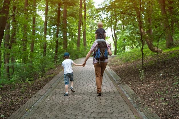 Papà con due bambini cammina nel parco. in viaggio con la famiglia. padre single. vista posteriore