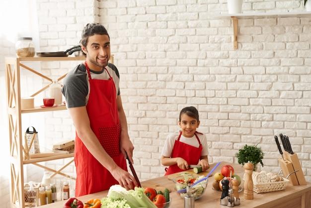 Papà con le verdure di taglio della figlia sulla cucina.