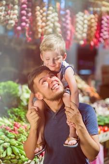 Papà con suo figlio al mercato agricolo.