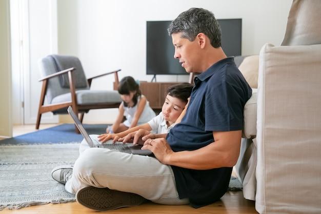 Papà concentrato e piccolo figlio seduti sul pavimento in appartamento, utilizzando laptop, lavorando o guardando contenuti.
