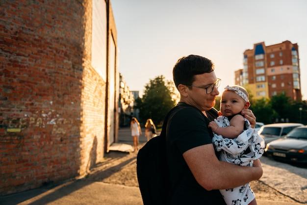 Papà del padre che tiene l'infante della ragazza di neonato sulle mani all'aperto sera di tramonto di estate