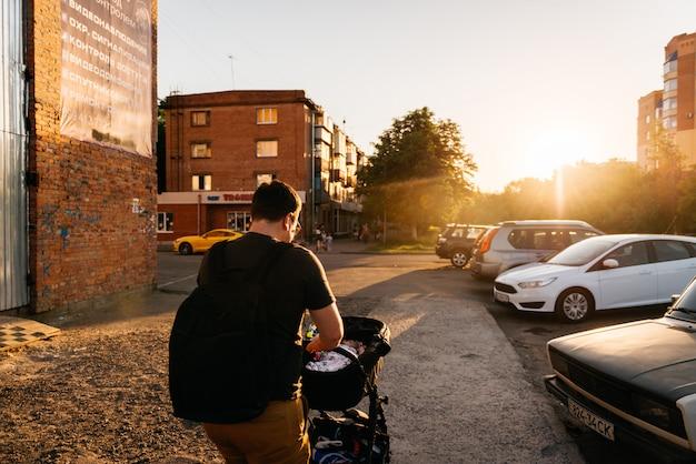 Papà del padre con il passeggiatore neonato della carrozzina fuori durante il tramonto di sera di estate