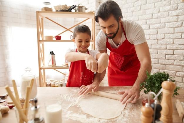 Papà e figlia stanno mettendo la farina su una pasta.
