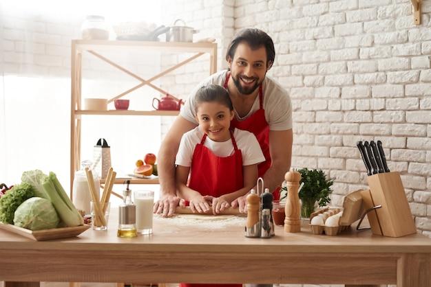 Papà e figlia stanno rotolando fuori pasta sulla cucina.