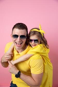 Papà e figlia svegli in giallo e occhiali da sole che abbracciano sul fondo rosa colorato. concetto di estate.