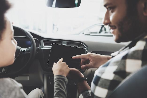 Papà e figlio controlla tablet per auto tocca schermo dispositivo.