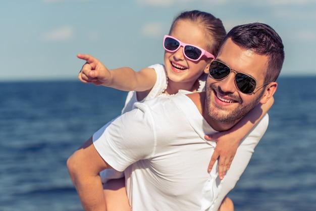 Papà e la sua piccola figlia in occhiali da sole stanno guardando altrove