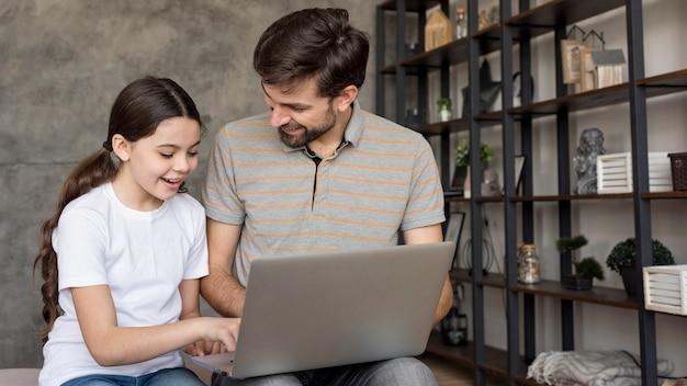 Papà e ragazza che per mezzo del computer portatile