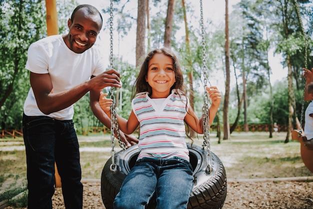 Papà è swinging daughter su tire swing in park